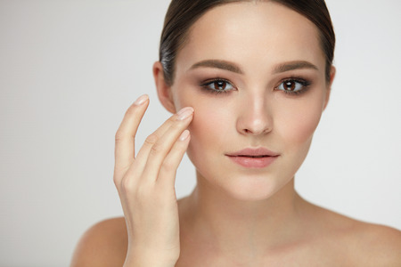 Cosmetic Face Care. Portrait Of Beautiful Girl Caressing Facial Skin Posing On Grey Background. Closeup Of Sexy Young Woman With Soft Clean Skin And Natural Makeup. Beauty Concept. High Resolution Imagens