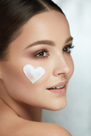 Beautiful Happy Woman With Heart Of Cream On Beauty Face Skin. Closeup Of Attractive Sexy Smiling Girl With Fresh Makeup And Heart-Shape Of Facial Cosmetic Product On Soft Smooth Skin. High Resolution Stock Photo