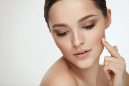 Beauty Skin Care. Portrait Of Beautiful Sexy Female Model Touching Soft Smooth Clean Pure Facial Skin With Finger. Closeup Of Healthy Young Woman With Natural Makeup. Cosmetic Concept. High Resolution Stock Photo