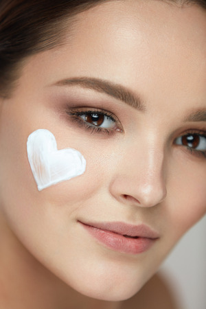 Beautiful Happy Woman With Heart Of Cream On Beauty Face Skin. Closeup Of Attractive Sexy Smiling Girl With Fresh Makeup And Heart-Shape Of Facial Cosmetic Product On Soft Smooth Skin. High Resolution Stok Fotoğraf