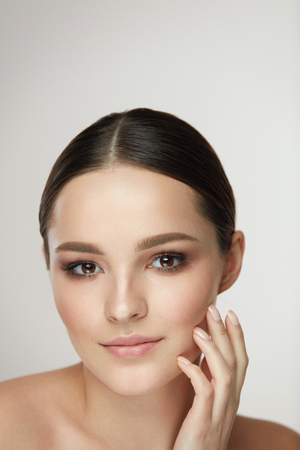 Cosmetic Face Care. Portrait Of Beautiful Girl Caressing Facial Skin Posing On Grey Background. Closeup Of Sexy Young Woman With Soft Clean Skin And Natural Makeup. Beauty Concept. High Resolution 스톡 콘텐츠