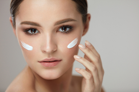 Woman Beauty Face Skin Care. Portrait Of Healthy Young Female Model With Soft Fresh Skin And Stripes Of Facial Cream On Cheeks. Closeup Beautiful Sexy Girl Applying Cosmetics On Skin. High Resolution