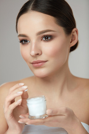 Face Beauty Care. Portrait Of Beautiful Young Woman With Facial Cream Jar In Hand. Closeup Of Sexy Female With Fresh Clean Soft Skin And Natural Makeup With Cosmetic Skin Care Product. High Resolution Banco de Imagens