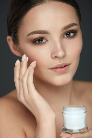 Face Skin Care. Portrait Of Beautiful Girl With Natural Makeup Holding Bottle Of Cream In Hand. Closeup Of Sexy Young Woman Putting Skin Cosmetics On Soft Smooth Facial Skin. Beauty. High Resolution Banco de Imagens