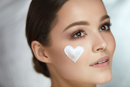 shaped: Woman Beauty Face Cosmetics. Closeup Sexy Smiling Female With Heart-Shaped Cosmetic Cream On Skin. Portrait Of Beautiful Happy Girl With Natural Makeup And Heart Sign On Soft Skin. High Resolution