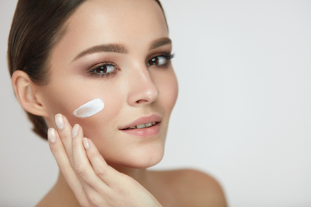 Beautiful Woman Face With Skin Care Cream On. Portrait Of Healthy Happy Female Applying Cream On Cheek. Closeup Beautiful Smiling Girl Putting Beauty Cosmetics On Fresh Soft Skin. High Resolution Stock Photo