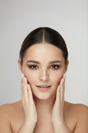 Beauty Woman Face. Portrait Of Healthy Sexy Girl Touching Fresh Soft Smooth Facial Skin With Hands. Closeup Of Beautiful Young Female Caressing Face With Natural Makeup. Cosmetics. High Resolution