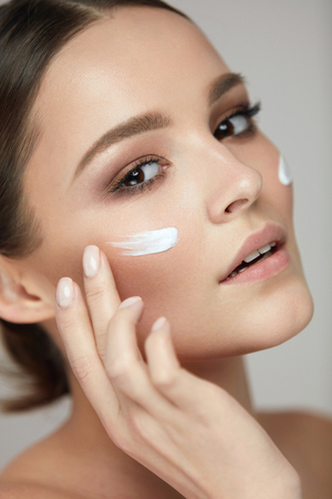 visage: Woman Beauty Face Skin Care. Portrait Of Healthy Young Female Model With Soft Fresh Skin And Stripes Of Facial Cream On Cheeks. Closeup Beautiful Sexy Girl Applying Cosmetics On Skin. High Resolution