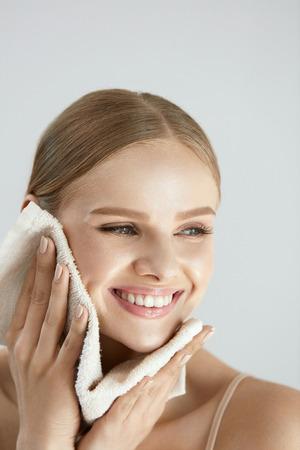 Lavage du visage. Gros plan d'une femme heureuse, sécher la peau avec une serviette. Haute résolution Banque d'images - 84130139