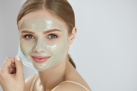 Face Mask. Closeup Portrait Of Beautiful Happy Smiling Girl Removing Peeling Cosmetic Beauty Mask From Healthy Facial Skin. High Resolution