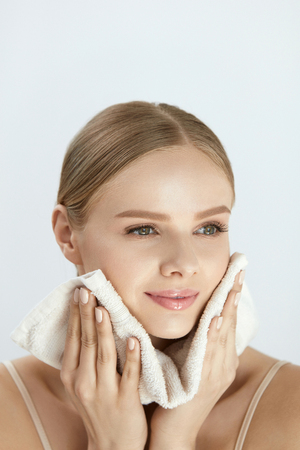 Woman Cleaning Face With White Towel. Closeup Portrait Of Beautiful Happy Smiling Young Female Wiping Facial Skin With Soft Facial Towel After Washing Face. High Resolution Stok Fotoğraf