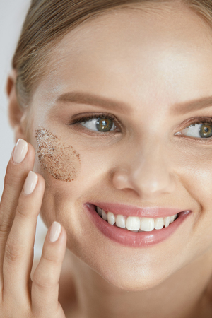 Beauty Skin Peeling. Closeup Smiling Female Applying Scrub On Face. High Resolution Stock Photo