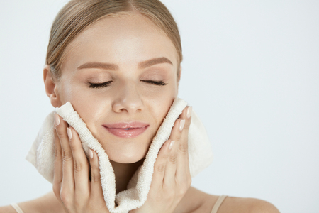 Woman Cleaning Face With White Towel. Closeup Portrait Of Beautiful Happy Smiling Young Female Wiping Facial Skin With Soft Facial Towel After Washing Face. High Resolution Archivio Fotografico