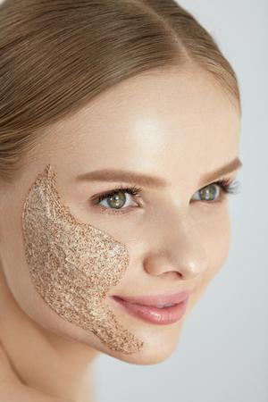 스킨 스크럽. 얼굴 피부에 화장품 필 링 마스크를 적용하는 아름 다운 행복 하 게 웃는 젊은 여자의 초상화. 높은 해상도 스톡 콘텐츠