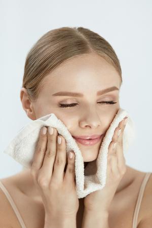 女性は、白いタオルで顔を洗浄します。幸せ笑顔若い女性拭き取り顔で美しい肌を洗顔後ソフト フェイス タオルのポートレート、クローズ アップ