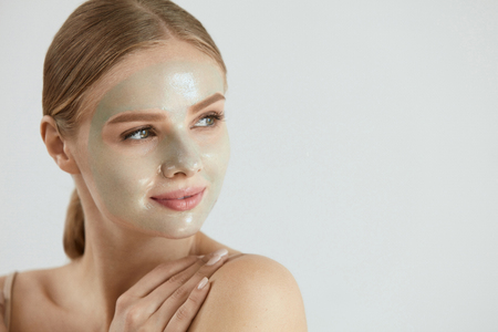 Face Care Mask. Closeup of Beautiful Sexy Smiling Young Woman With Peeling Mask On Facial Skin. High Resolution Stock Photo