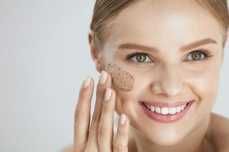 Frote la piel de la cara. Retrato De Hermosa Hembra Sonriente Aplicando Máscara Cosmética, Exfoliante En La Piel Facial. Alta resolución