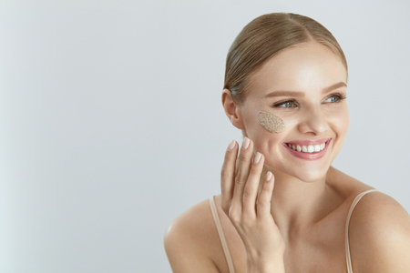 Face Skin Scrub. Portrait Of Beautiful Smiling Female Applying Cosmetic Mask, Face Scrub On Facial Skin. High Resolution
