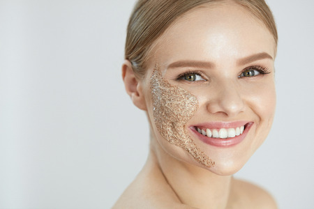 Face Skin Cleaning. Closeup Portrait Of Attractive Smiling Young Woman With Exfoliating Peach Scrub On Facial Skin. High Resolution Stock Photo