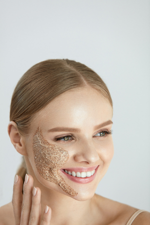 Face Skin Care. Closeup Portrait Of Beautiful Happy Smiling Female With Cleansing Facial Scrub Mask On Cheek. High Resolution Stock Photo - 84130197