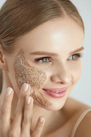 顔のスキンケア。クレンジング洗顔スクラブ マスクの頬に美しい幸せな笑みを浮かべて女性のポートレート、クローズ アップ。高分解能