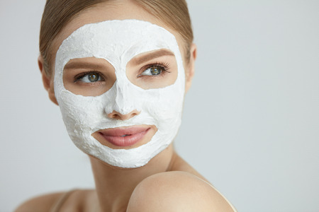 Skin Care Mask. Closeup Portrait Of Attractive Smiling Young Woman With White Clay Facial Mask On Healthy Fresh Face Skin. High Resolution