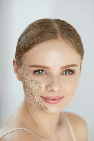Face Skin Scrub. Portrait Of Beautiful Happy Smiling Young Woman Applying Cosmetic Peeling Mask On Facial Skin. High Resolution Фото со стока