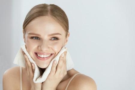 Pulizia della pelle del viso. Ritratto del primo piano di bella ragazza sorridente felice che tiene asciugamano bianco pulito vicino alla pelle facciale dopo aver lavato il viso. alta risoluzione Archivio Fotografico - 84130210