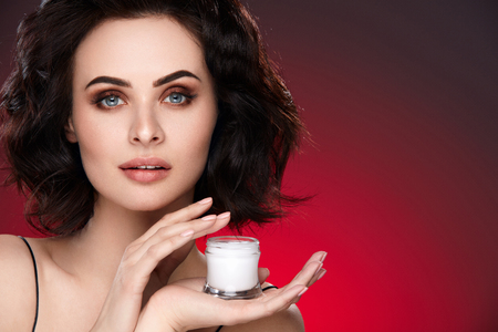 Woman Skin Beauty. Portrait Of Attractive Female With Sexy Makeup And Hairstyle Holding Face Cream Bottle. High Resolution
