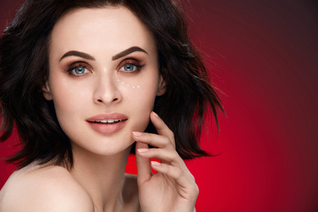 女性美の肖像画。短い暗い茶色の髪と明るい化粧赤の背景に顔の皮膚に触れると美しい若い女性。高分解能