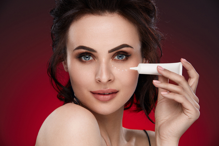 Eye Skin Care. Portrait Of Beautiful Sexy Woman With Fresh Natural Makeup Applying Eye Cream From White Tube On Skin Under Eyes. High Resolution