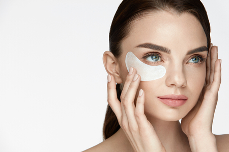 Eye Skin Care. Portrait Of Beautiful Happy Smiling Young Female Applying Cosmetic Beauty Product, Under Eye Mask Patch On Facial Skin On White Background. High Resolution