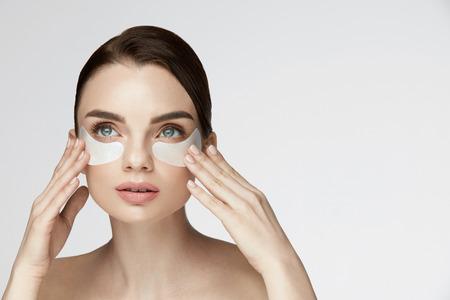 Beauty Face Huidverzorging. Close-up van jonge vrouw met mooie grote ogen, natuurlijke make-up en frisse gezichtshuid aanbrengen van onder-oog-patches op gezicht. Hoge resolutie