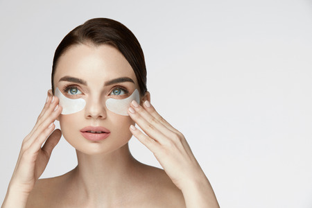 Beauty Face Skin Care. Closeup Of Young Woman With Beautiful Big Eyes, Natural Makeup And Fresh Facial Skin Applying Under-eye Patches On Face. High Resolution 版權商用圖片