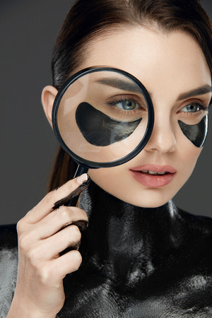 Eye Skin Treatment. Beautiful Female Face With Mask And Patches. Beautiful Woman With Fashionable Makeup Holding Magnifying Glass Near Eye. High Resolution