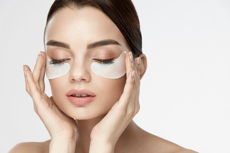 눈 피부 마스크. 뷰티 얼굴에 눈 스킨 패치, 스킨 케어 제품 아래 흰색으로 아름 다운 젊은 여성 모델의 초상화. 높은 해상도