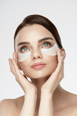 undereye: Beauty Face Skin Care. Closeup Of Young Woman With Beautiful Big Eyes, Natural Makeup And Fresh Facial Skin Applying Under-eye Patches On Face. High Resolution Stock Photo
