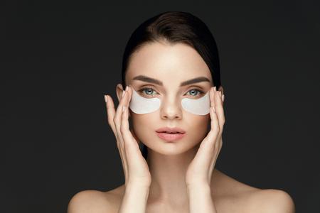 目の治療中です。目の下のパッチで女性の顔。黒の背景に目の下に美容パッチを適用する新鮮な柔らかい肌と美しい若い女性。高解像度 写真素材