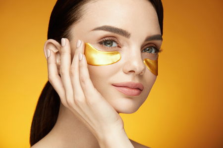 Eye Skin Care Patches. Closeup Of Beautiful Smiling Girl Applying Gold Patches, Collagen Under Eye Mask On Face. Beauty Cosmetics. High Resolution