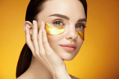 Oogverzorgingspatches. Close-up van mooi glimlachend meisje die gouden flarden toepassen, collageen onder oogmasker op gezicht. Schoonheid Cosmetica. Hoge resolutie