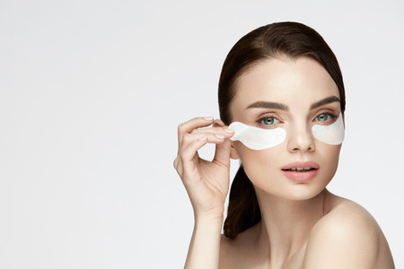 Woman Beauty Face With Mask Under Eyes. Closeup Of Beautiful Sexy Young Female With Fresh Facial Skin And Natural Makeup And Patches Under Eyes. High Resolution
