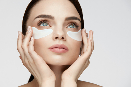 Eye Skin Treatment. Portrait Of Beautiful Young Woman With Natural Makeup Applying White Under Eye Patches, Beauty Mask On Face. High Resolution Stock Photo