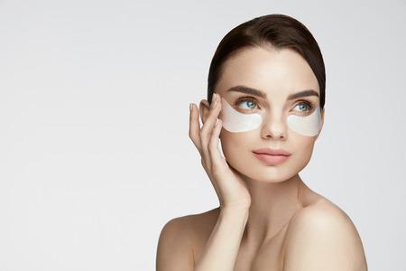 눈 피부 미용. 자연 얼굴 메이크업 및 흰색 배경에 얼굴에 눈 케어 제품 아래 아름 다운 젊은 여성 모델의 초상화. 높은 해상도 스톡 콘텐츠