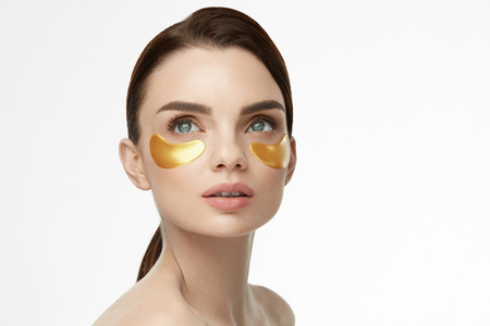 Cara de mujer belleza con máscara debajo de los ojos. Hermosa mujer con maquillaje natural y parches de colágeno de oro en la piel facial fresca. Alta resolución Foto de archivo