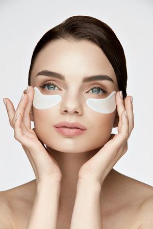 Augenhautbehandlung. Portrait der schönen jungen Frau mit natürlichem Make-up, das Weiß unter Augen-Flecken, Schönheits-Maske auf Gesicht anwendet. Hohe Auflösung Standard-Bild - 85441678