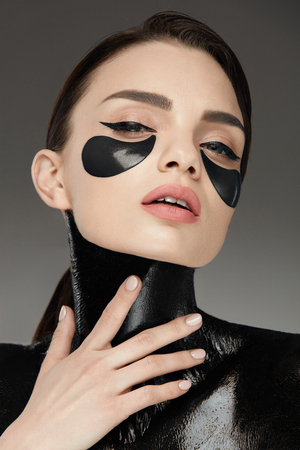 Skin Care Mask. Woman With Black Mask On Body And Under Eye Patches On Beautiful Face Touching Her Skin With Hand. High Resolutions Stock Photo