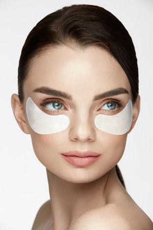 Face Skin Care. Closeup Of Attractive Young Female Model With Natural Makeup And Mask Under Eyes, Cosmetic Eye Patches On Facial Skin. High Resolution Stock Photo