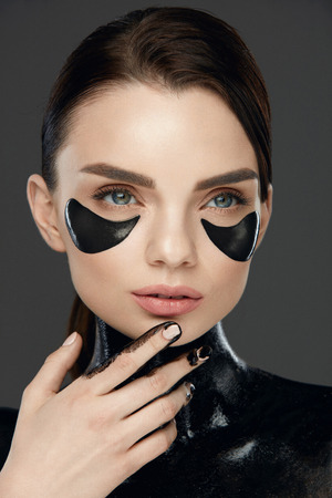 Woman Face With Mask And Patches Under Eyes. Beautiful Fashionable Female Model With Black Eye Pads Applying Black Mask On Neck Skin. Beauty Care. High Resolution Stock Photo