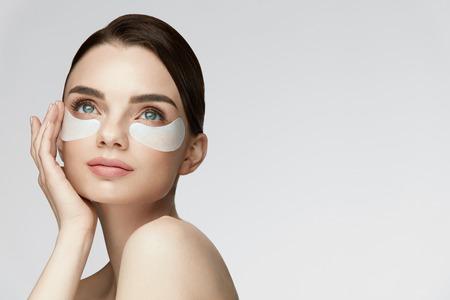 Belleza de la piel de los ojos. Retrato de la hermosa modelo de mujer joven con maquillaje facial natural y producto para el cuidado de los ojos en la cara sobre fondo blanco. Alta resolución Foto de archivo - 85441692