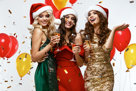 New Year's Party Time. Happy Girls Having Fun At Party. Sexy Smiling Young Women Dressed In Santa Hats And Fashionable Bright Dresses Holding Champagne Glasses At Celebration. High Quality Image.
